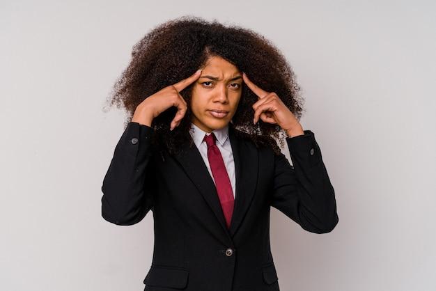 Giovane donna d'affari afroamericana che indossa un abito isolato su sfondo bianco focalizzato su un compito, mantenendo gli indici puntati verso la testa.