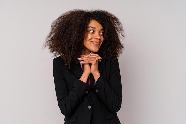 La giovane donna d'affari afroamericana che indossa un abito isolato su sfondo bianco tiene le mani sotto il mento, sta guardando felicemente da parte.