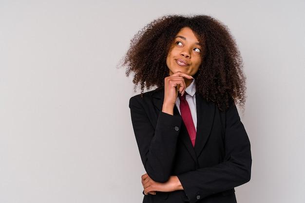 Giovane donna d'affari afroamericana che indossa un abito isolato su sfondo bianco guardando lateralmente con espressione dubbiosa e scettica.