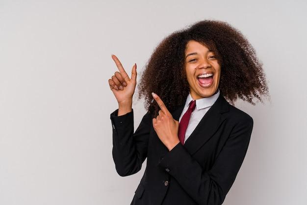 Giovane donna d'affari afroamericana che indossa un abito isolato su sfondo bianco che punta con l'indice a uno spazio di copia, esprimendo eccitazione e desiderio.