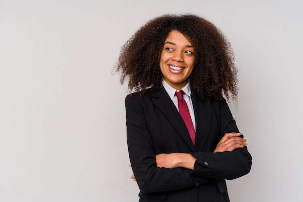 Giovane donna d'affari afroamericana che indossa un abito isolato su sfondo bianco sorridente fiducioso con le braccia incrociate.