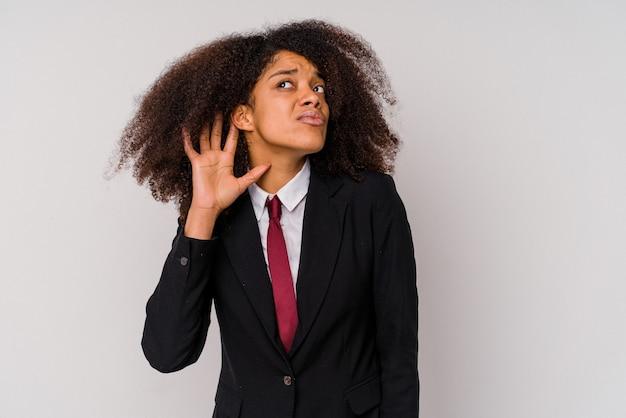 Giovane donna d'affari afroamericana che indossa un abito isolato su sfondo bianco cercando di ascoltare un pettegolezzo.