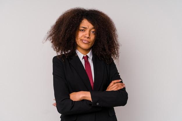 Giovane donna d'affari afroamericana che indossa un abito isolato su sfondo bianco infelice guardando a porte chiuse con espressione sarcastica.