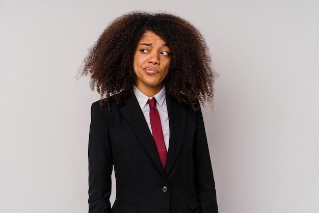 La giovane donna d'affari afroamericana che indossa un abito isolato su bianco confuso, si sente dubbiosa e insicura.