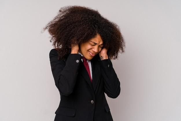 Giovane donna d'affari afroamericana che indossa un abito isolato su bianco che copre le orecchie con le mani.