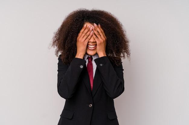 La giovane donna d'affari afroamericana che indossa un abito isolato su bianco copre gli occhi con le mani, sorride ampiamente in attesa di una sorpresa.