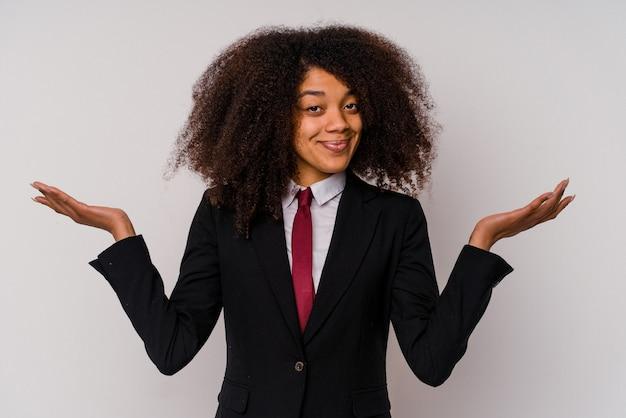 Giovane donna d'affari afroamericana che indossa un abito isolato su bianco dubitando e alzando le spalle nel gesto interrogativo.