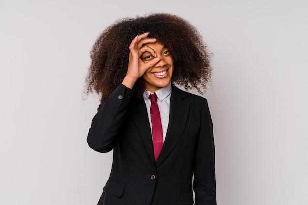La giovane donna afroamericana di affari che porta un vestito isolato su bianco eccitato mantenendo il gesto giusto sull'occhio.
