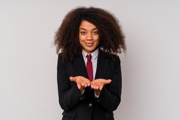 Giovane donna afroamericana di affari che indossa un vestito isolato su bianco che tiene qualcosa con le palme