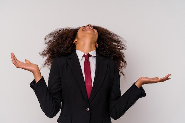 Giovane donna d'affari afroamericana che indossa un abito isolato su bianco urlando al cielo, alzando lo sguardo, frustrata.