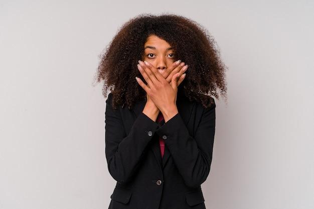 Giovane donna d'affari afroamericana che indossa un abito isolato su bianco scioccato che copre la bocca con le mani.