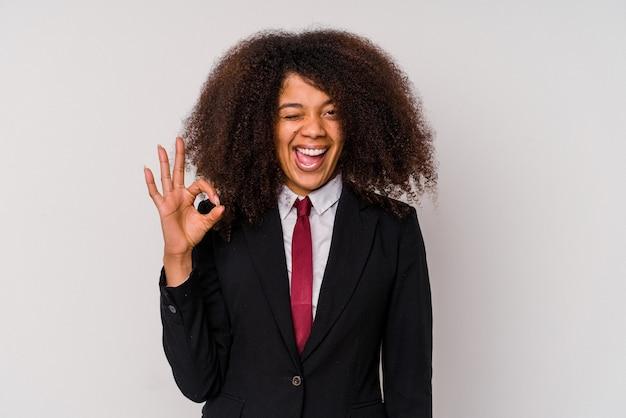 La giovane donna afroamericana di affari che porta un vestito isolato su bianco strizza l'occhio e tiene un gesto giusto con la mano.