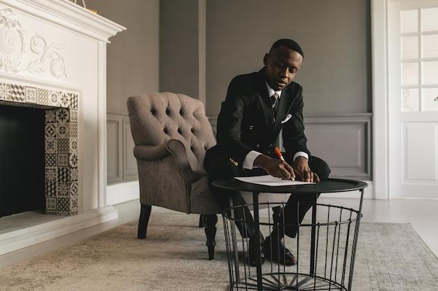 Giovane uomo d'affari afroamericano in tailleur che prende appunti foto di alta qualità