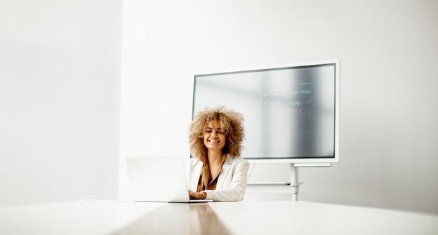 Giovane donna di affari afroamericana che si siede e che lavora al computer portatile nell'ufficio moderno
