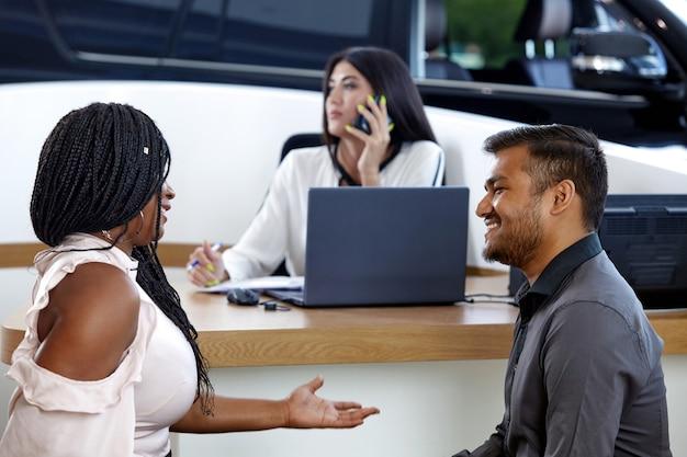 Una giovane coppia afroamericana comunica sullo sfondo di un agente di vendita di auto