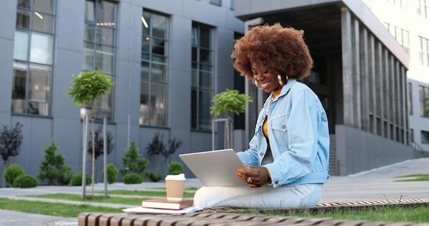 Giovane bella donna riccia afroamericana che si siede sulla panchina, parlando tramite webcam sul computer portatile e ridendo all'aperto. videochatting abbastanza femminile in strada. videochat.