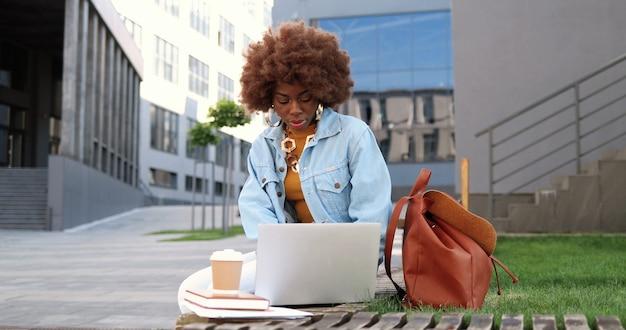 Giovane bella donna riccia afroamericana che si siede sulla panchina, lavorando su un computer portatile e bevendo caffè all'aperto.