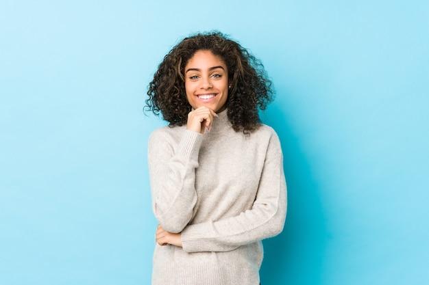 Giovane donna afroamericana capelli ricci sorridente felice e fiduciosa, toccando il mento con la mano.
