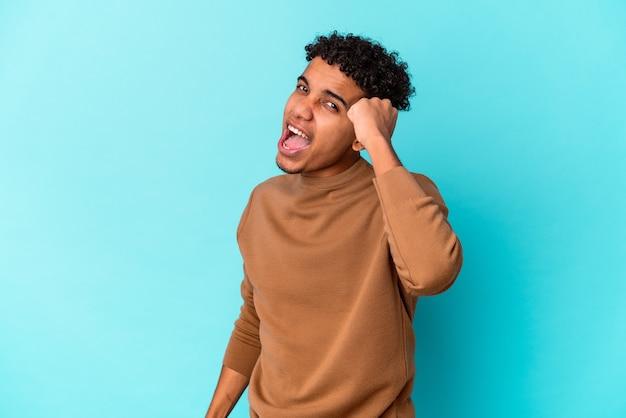Giovane uomo riccio afroamericano isolato sull'azzurro che celebra una vittoria, passione ed entusiasmo, felice espressione.