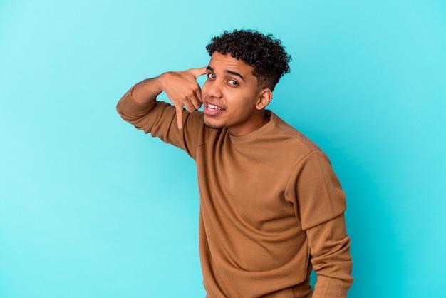 Giovane uomo afroamericano riccio isolato sull'azzurro che mostra un gesto di chiamata di telefono cellulare con le dita.