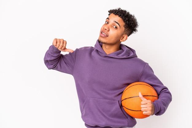 Il giovane uomo riccio afroamericano isolato giocando a basket si sente orgoglioso e sicuro di sé, esempio da seguire.