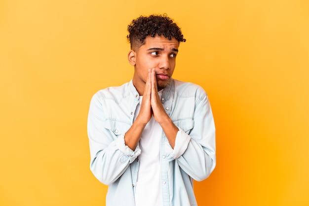 Giovane uomo afroamericano riccio isolato sulla preghiera viola, mostrando devozione, persona religiosa in cerca di ispirazione divina.
