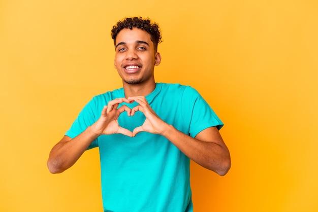 Giovane uomo afroamericano riccio isolato su viola sorridente e mostrando una forma di cuore con le mani.