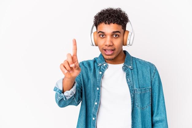 Giovane uomo riccio afroamericano che ascolta la musica con le cuffie che mostrano il numero uno con il dito.