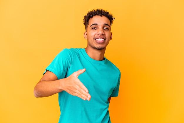 Giovane uomo afroamericano riccio su viola che allunga la mano alla macchina fotografica nel gesto di saluto.