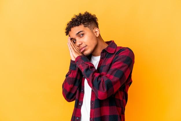 Giovane uomo afroamericano riccio su giallo che sbadiglia mostrando un gesto stanco che copre la bocca con la mano.
