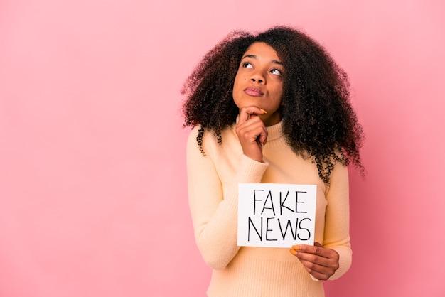Giovane donna afroamericana riccia che tiene una notizia falsa su un cartello che guarda lateralmente con espressione dubbiosa e scettica.