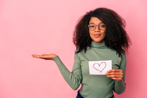 Giovane donna riccia afroamericana che tiene un simbolo del cuore sul cartello che mostra uno spazio della copia su una palma e che tiene un'altra mano sulla vita.