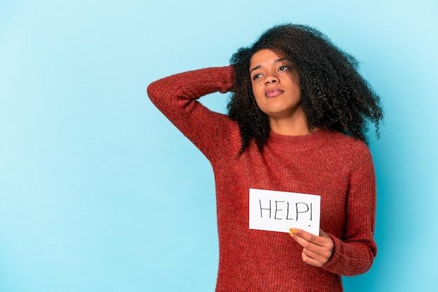 Giovane donna afroamericana riccia che tiene un cartello di aiuto che tocca la parte posteriore della testa, pensando e facendo una scelta.