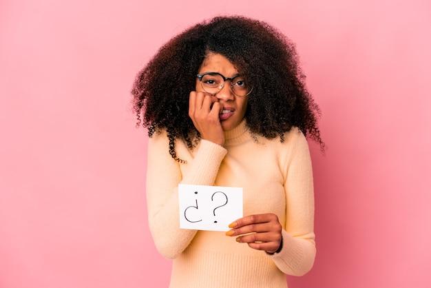 Giovane donna afroamericana riccia che tiene un interrogatorio su un cartello che si morde le unghie, nervosa e molto ansiosa.
