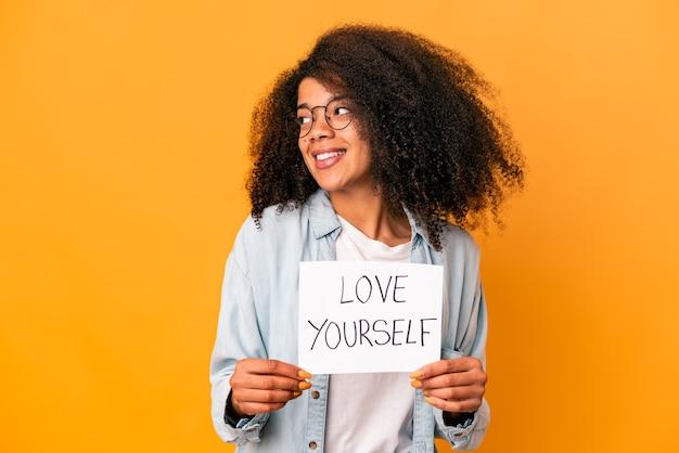 La giovane donna riccia afroamericana che tiene un cartello di amore te stesso guarda da parte sorridente, allegra e piacevole.