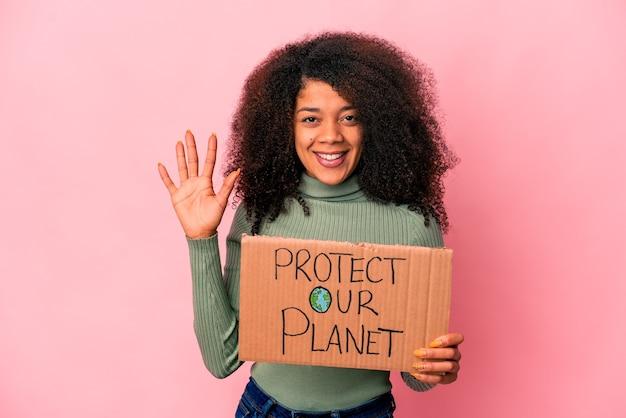 Giovane donna riccia afroamericana che tiene un banner di proteggere il nostro pianeta
