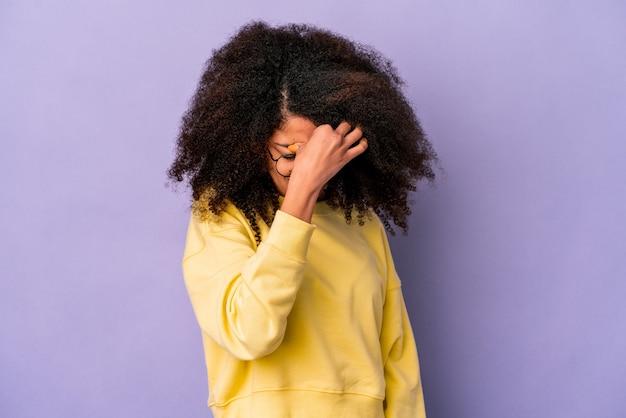 Giovane donna afroamericana riccia isolata sulla parete viola, avendo un mal di testa, toccando la parte anteriore del viso.