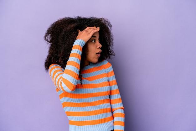 Giovane donna riccia afroamericana su viola che guarda lontano tenendo la mano sulla fronte.