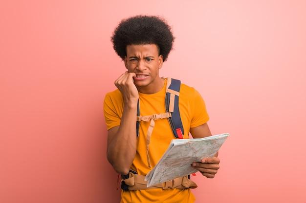 Uomo giovane esploratore afroamericano che tiene una mappa che morde le unghie, nervoso e molto ansioso