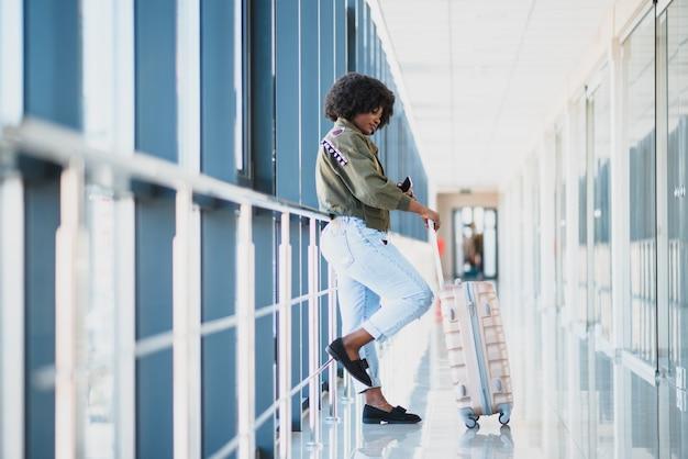 Il giovane passeggero afroamericano femminile in abbigliamento casual è in aeroporto con i bagagli
