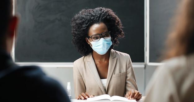 Giovane insegnante femminile afroamericano in occhiali e mascherina medica che si siede al tavolo a scuola in classe, leggendo libri di testo e insegnando. lezione di letteratura. educatrice donna davanti a studenti o alunni.