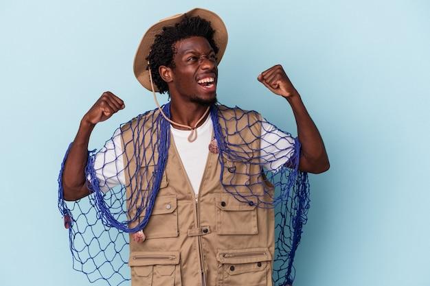 Giovane pescatore afroamericano che tiene una rete isolata su fondo blu che alza il pugno dopo una vittoria, concetto del vincitore.