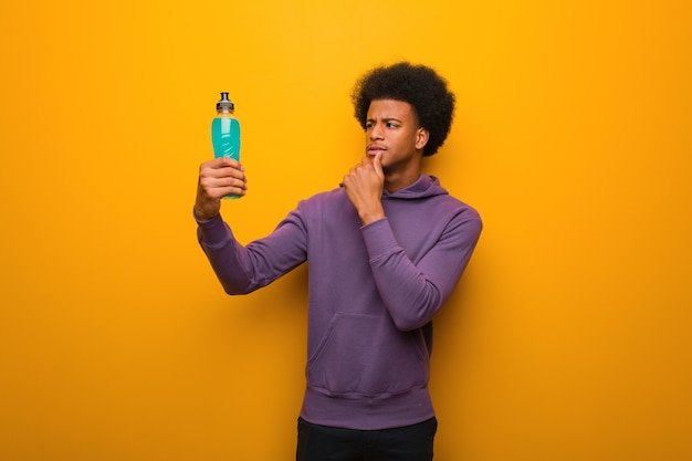 Giovane uomo afroamericano di forma fisica che tiene una bevanda energetica dubitando e confuso