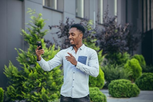 Giovane freelance afroamericano che parla in videochiamata vicino all'ufficio allegro uomo sorridente
