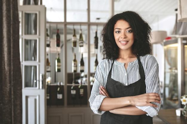 Giovane ragazza afroamericana in grembiule in piedi con le braccia piegate nel ristorante. bella ragazza con i capelli ricci scuri in piedi in grembiule al caffè