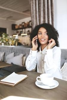 Giovane ragazza afroamericana che si siede nel ristorante e che parla sul suo telefono cellulare. ragazza con capelli ricci scuri che si siede nella caffetteria con una tazza di caffè e menu sul tavolo