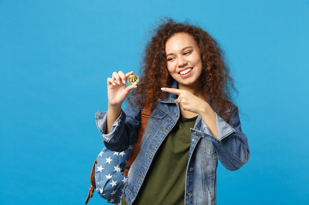 Giovane studentessa adolescente afroamericana in vestiti di jeans, zaino tenere bitcoin isolato sulla parete blu