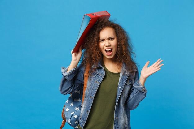 Giovane studentessa teenager della ragazza afroamericana in cartella della tenuta dello zaino dei vestiti del denim isolata sulla parete blu