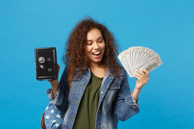 Giovane studentessa adolescente afroamericana in vestiti di jeans, zaino in sicurezza isolato su parete blu