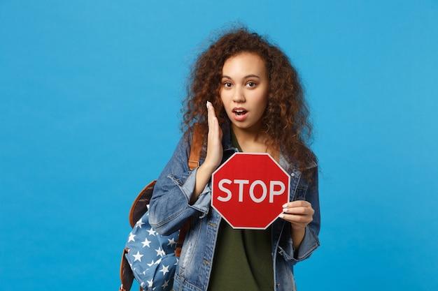 Giovane studentessa adolescente afroamericana in vestiti di jeans, fermata della tenuta dello zaino isolata sulla parete blu